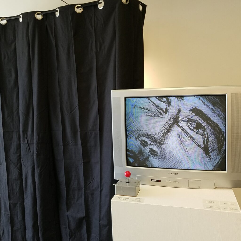 A live view camera sits on an x/y gantry. Viewer can navigate the drawings behind the curtain by commandeering the joysticks.
